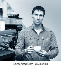 Young barista standing coffee maker on background