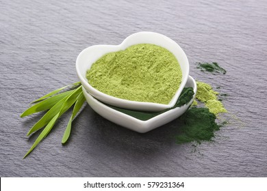 Young barley grass and powder and spirulina in heart shaped bowl on concrete background. Detox and healthy living.