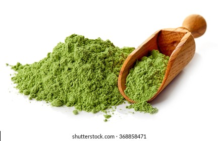 Young barley or wheat grass with wodden shovel, detox superfood, white background