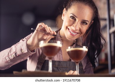 Young barmaid smiles after making two espresso martini short drinks with a coffee.