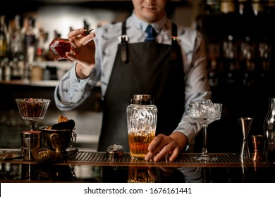 young barman adds ingredient for cocktail to glass shaker. Shelves with bottles of alcohol in background.