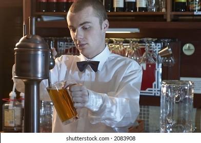 young barman at a bar counter pouring beer