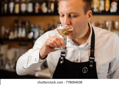 Young barman dressed in a white shirt drinking alcoholic cocktail with green olives on the background of bar