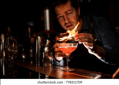 Young barman making a fresh alcoholic cocktail with a smoky note on the bar counter