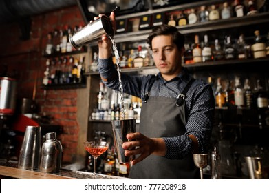 Young barman pouring alcoholic drink from one metal glass into another on the background of bar counter