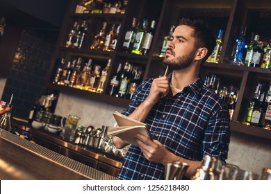 Young barman standing at bar counter holding notebook looking aside thinking