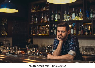 Young barman standing leaning on bar counter looking down thoughtful