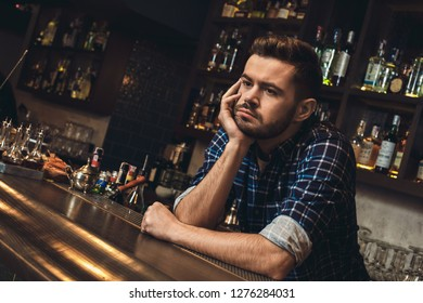 Young barman standing leaning on bar counter looking aside bored close-up