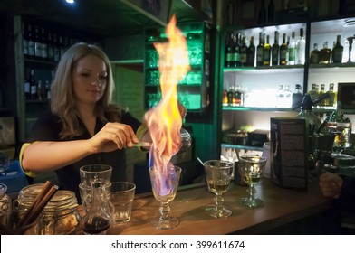 A young bartender girl in a Czech bar Absintherie in central Prague showing absinthe drink preparation. Absinthe proper drinking stock photo image. Absinthe Museum, Prague, Czech republic.