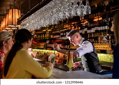 Young bartender making a cocktail out of a coktail shaker at the bar counter.