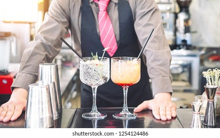 Young bartender making cocktails at bar counter - Barman serving drinks - Work, passion and mixologist concept