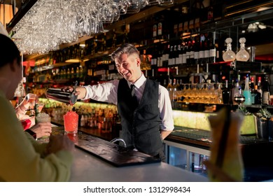 Young bartender pouring a cocktail out of a coktail shaker at the bar counter.