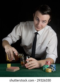 Young bartender pouring whiskey at the casino table with deck of cards and chips