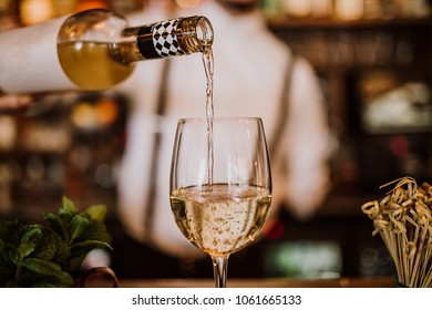 Young bartender pouring white wine from a bottle into a wine glass, selective focus point on the wine glass, close up view