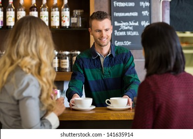 Young bartender serving coffee to female friends at cafe