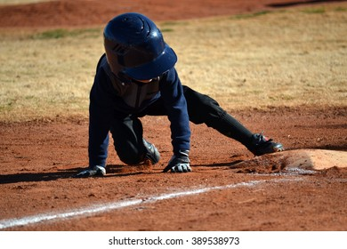 Young baseball player on ground with foot on third base