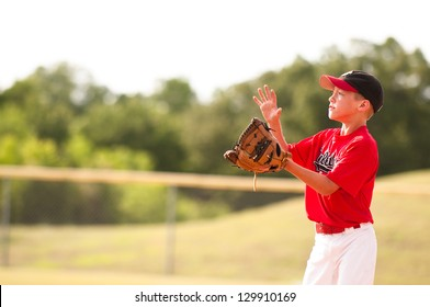 Young baseball player in red jersey about to catch the pop fly.
