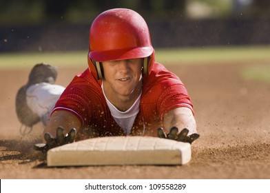 Young baseball player sliding towards second base on field