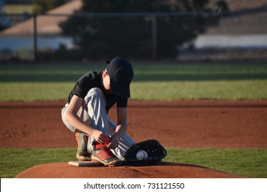 Young baseball playing stopping to tie shoe laces on pitcher's mound
