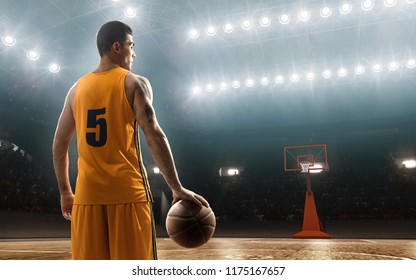 Young basketbal player on professional court holding a ball. Backview