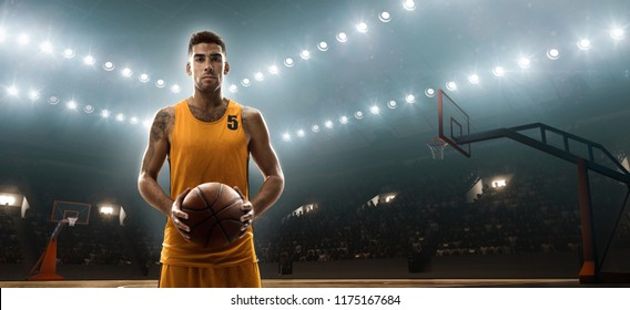 Young basketbal player on professional sports arena holds a ball