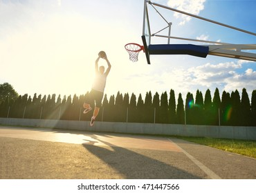 A young basketball player flying towards the rim for a slam dunk.