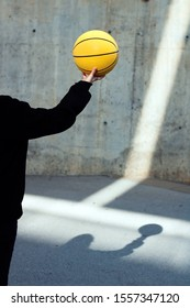 Young basketball player girl dressed in a black hoodie taking a yellow basketball. Sport concept.