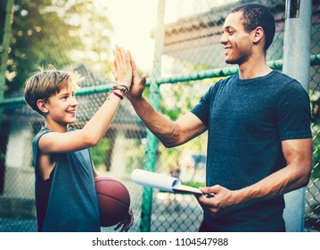 Young basketball player and his coach