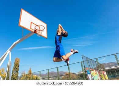 Young Basketball street player making slam dunk