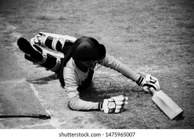 Young batsman lying on the ground unique black and white photo