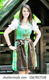 young bavarian woman wearing a dirndl standing at wooden lodge