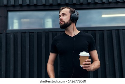 Young beard handsome man drinking coffee and listening music in headphones, posing in the street, outdoor hipster portrait,glass talking on the phone, wearing sunglasses works in company, USA,hipster