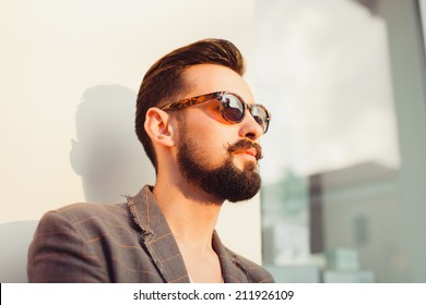 young beard man posing in the street, fashion style, vintage glasses, sunglasses, mustache
