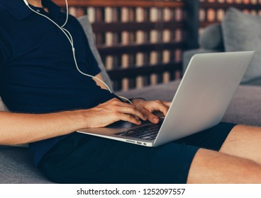 Young beard man using laptop on office, freelance work, outdoor close up hipster portrait, brutal, guy listening music on earphones, make photo and video, production, Bali