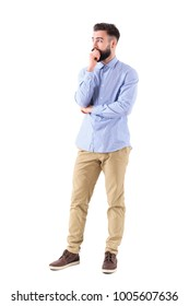 Young bearded adult business man in formalwear thinking and looking up with hand on chin. Full body length portrait isolated on white background.
