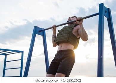 Young bearded athlete training outdoor with weighted vest,  exercise with military plate carrier