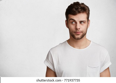 Young bearded attractive male with skeptic look, raises eyebrow in bewilderment, has some doubts and uncertainty, looks curiously aside, isolated over white background with copy space for text