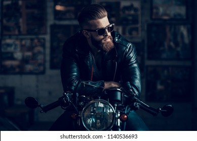 Young Bearded Biker Sitting on Motorcycle in Garage. Indoor Garage. Young Mechanic in Garage. Parts of Motorcycle. Man in Checkered Shirt. Man on Vintage Bike. Biker Lifestyle Concept.