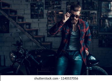 Young Bearded Biker in Sunglasses Sitting on Motorcycle in Garage. Indoor Garage. Young Mechanic in Garage. Parts of Motorcycle. Man in Checkered Shirt. Man on Vintage Bike. Biker Lifestyle Concept.