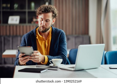 Young bearded blogger dressed smart casual using tablet and sitting in cafe. On deska are agenda, coffee and laptop. - Shutterstock ID 1390252169