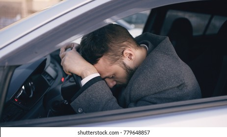 Young bearded business man sitting in car very upset and stressed after hard failure and moving in traffic jam
