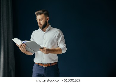Young bearded businessman, dressed in a white shirt standing near the window on a dark blue wall and reading a book. A man stands and holds the thick book in hands.