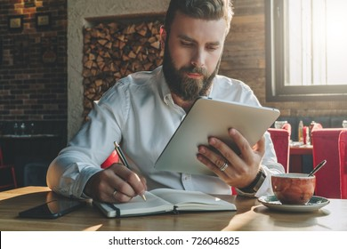 Young bearded businessman sits in cafe, home at table, looking at screen of tablet computer and writes in notebook.Man is working, studying.Online education,marketing, training. E-learning,e-commerce.