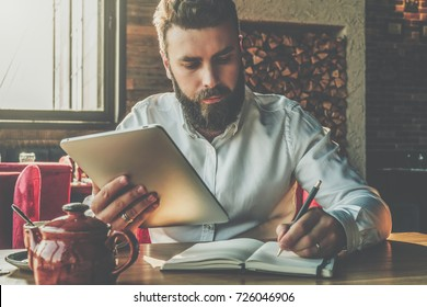 Young bearded businessman sits in cafe at table, holding tablet computer and writes in notebook. Man is working, studying.Online education, marketing, training.E-learning,e-commerce. Instagram filter.