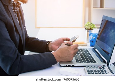 Young bearded businessman sits in office at table and uses smart