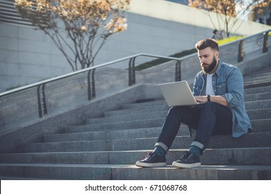Young bearded businessman sits on steps, using laptop and looks on his screen.Hipster man is working, blogging, chatting online,checking email. Student learning online. Summer sunny day. Lifestyle.
