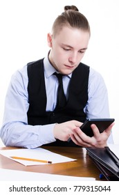Young bearded businessman sits at tablet