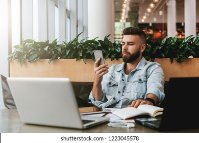 Young bearded businessman is sitting in cafe at table in front of laptops,using smartphone. Remote work.Hipster man blogging, chatting, cheking email. Student learning online. Education for adult.