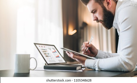 Young bearded businessman sitting at desk in front of laptop with graphis, charts, diagrams on screen, making notes in tablet computer. Freelancer works remotely. Student learning online. E-commerce.