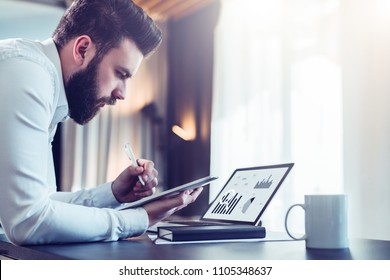 Young bearded businessman sitting at desk in front of laptop with graphis, charts, diagrams on screen, making notes in digital tablet. Freelancer works. Student learning online. Online marketing.